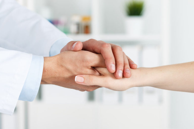 Friendly male doctor's hands holding female patient's hand for encouragement and empathy. Partnership, trust and medical ethics concept.
